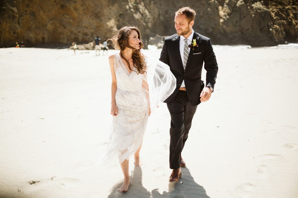 A wedding couple is walking along the beach and smiling at each other.
