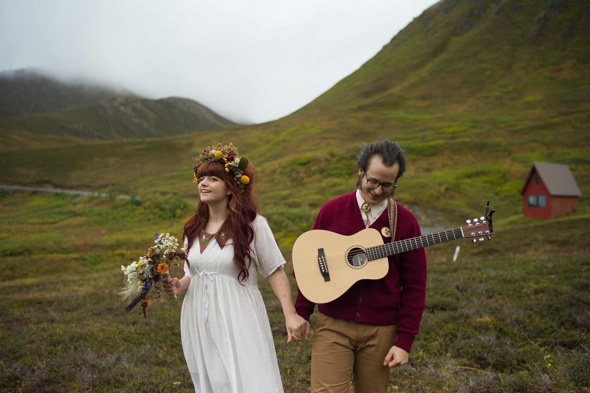 A wedding couple is walking through a meadow in the mountains and holding hands.