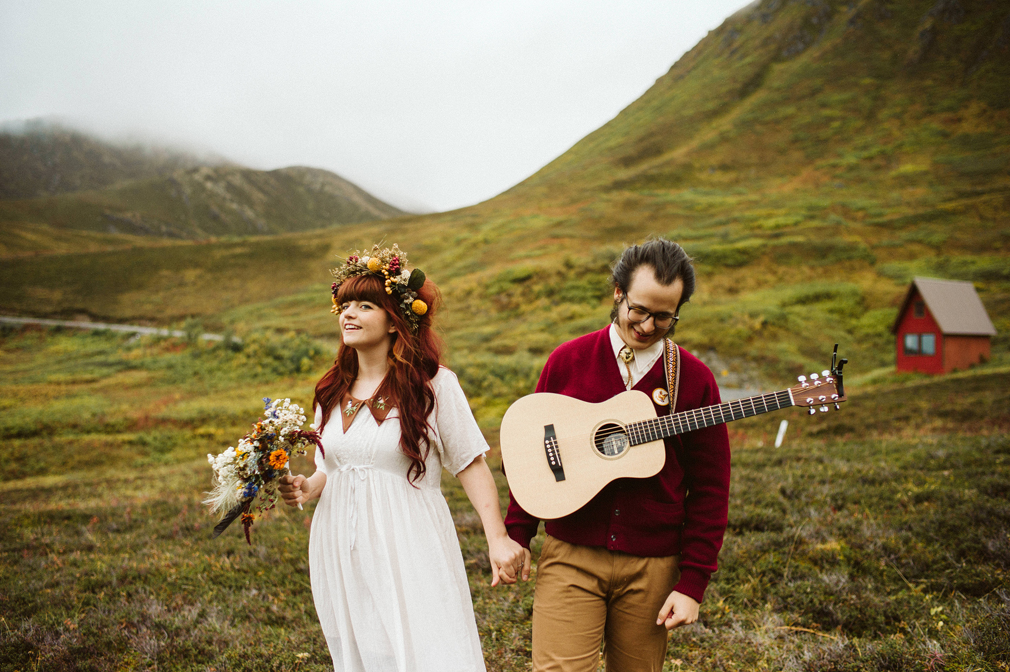 A wedding couple is holding hands and walking through a meadow in the mountains.