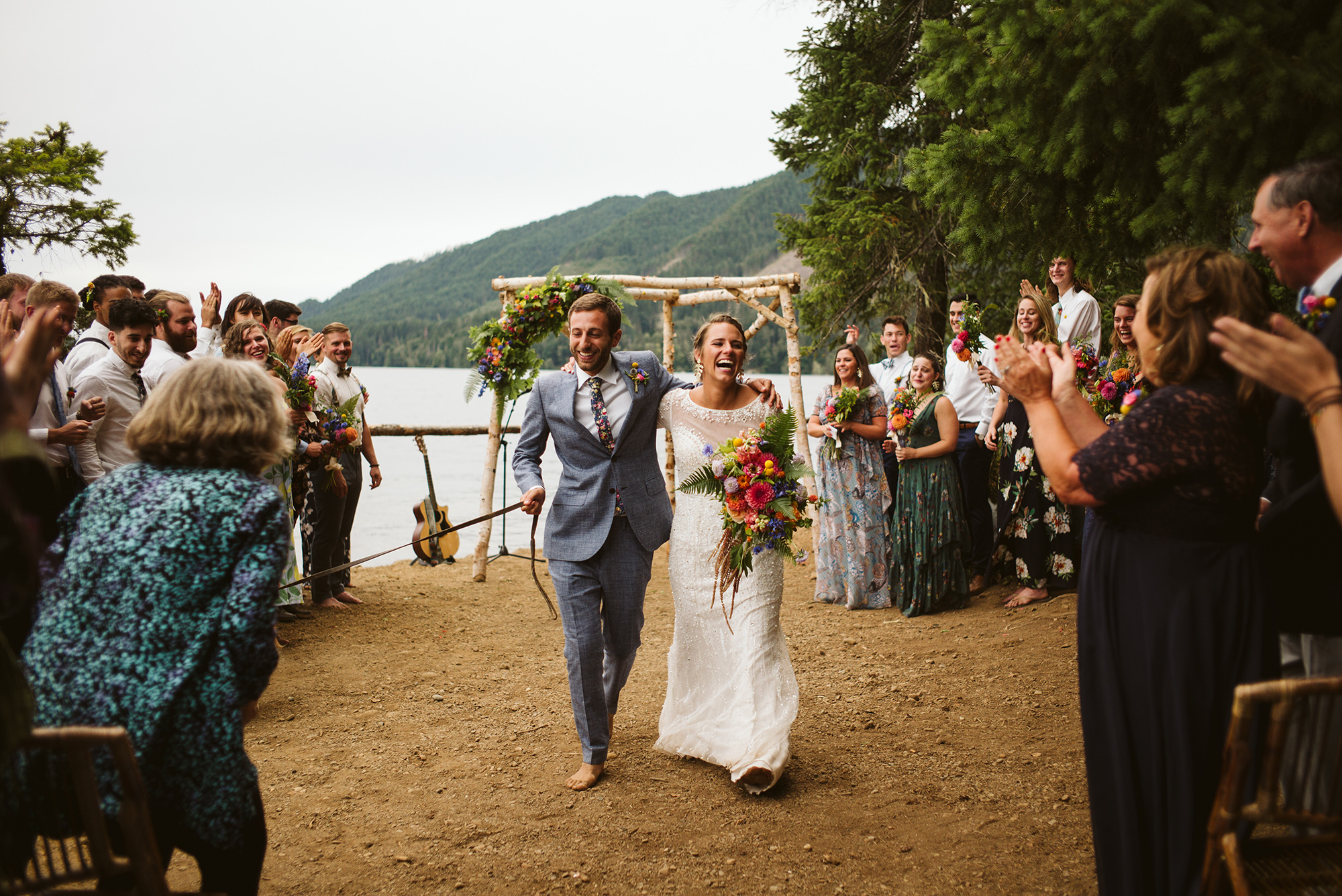 A wedding couple is walking down the aisle with their guests cheering at them.