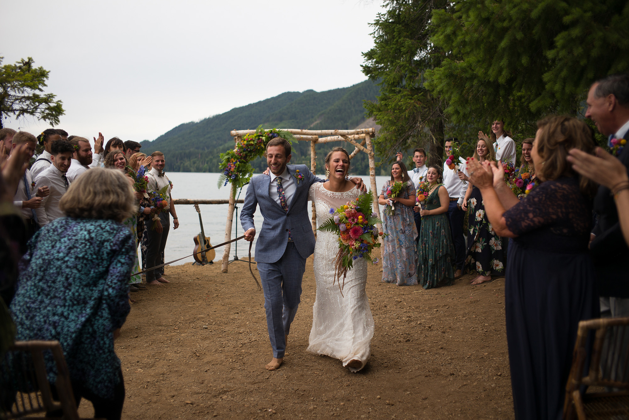 A wedding couple is walking down the aisle with their guests cheering next to them.