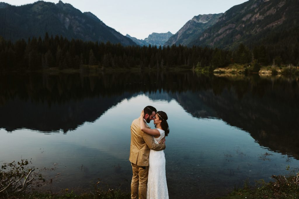 A wedding couple is holding each other and standing in front of a lake, with mountains and trees surrounding it.
