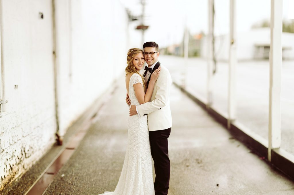 A wedding couple is holding each other and standing next to an industrial building.