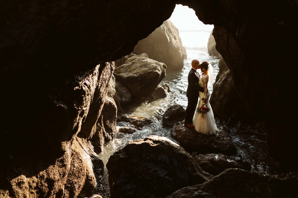 A groom his kissing his bride on the forehead and they are standing in a cave.