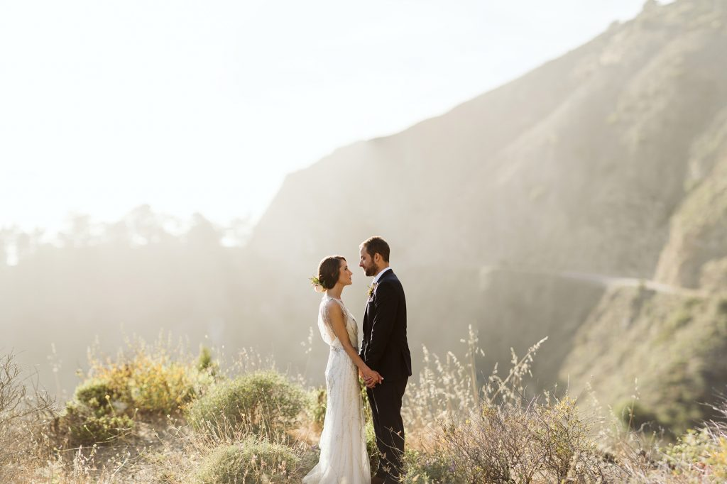 A wedding couple is holding each other and standing on a mountain.