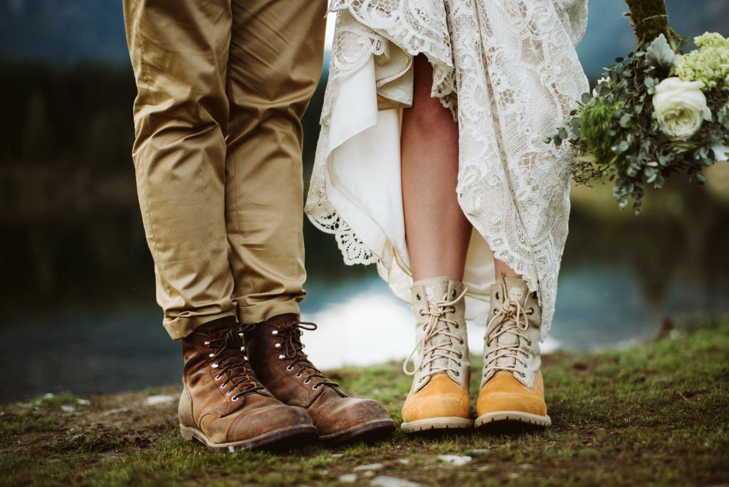 A closeup of a wedding couple wearing their hiking shoes and standing on a rock.