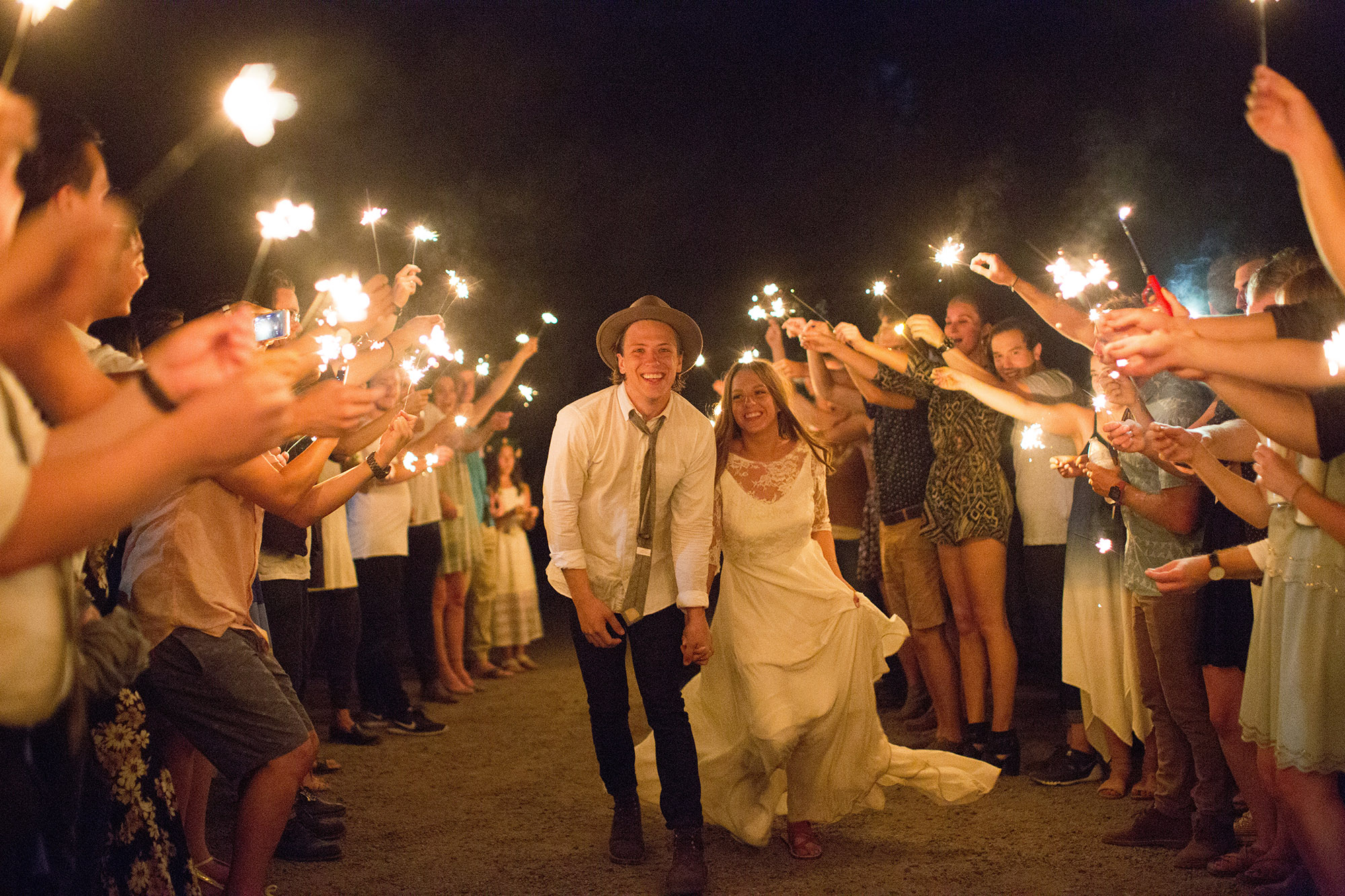 A wedding couple is holding hands and their guests are standing around them holding sparklers.