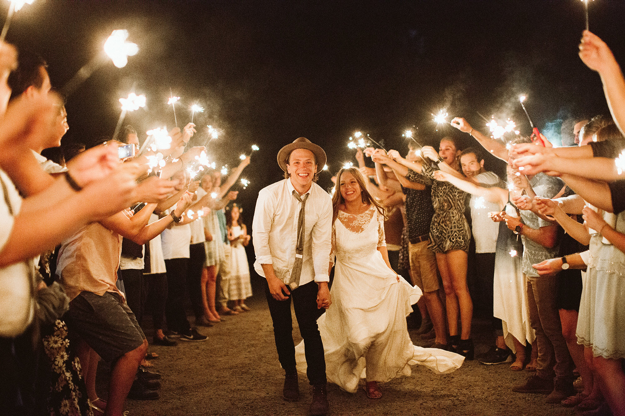 A wedding couple is walking along an aisle and their guests are holding up sparklers.