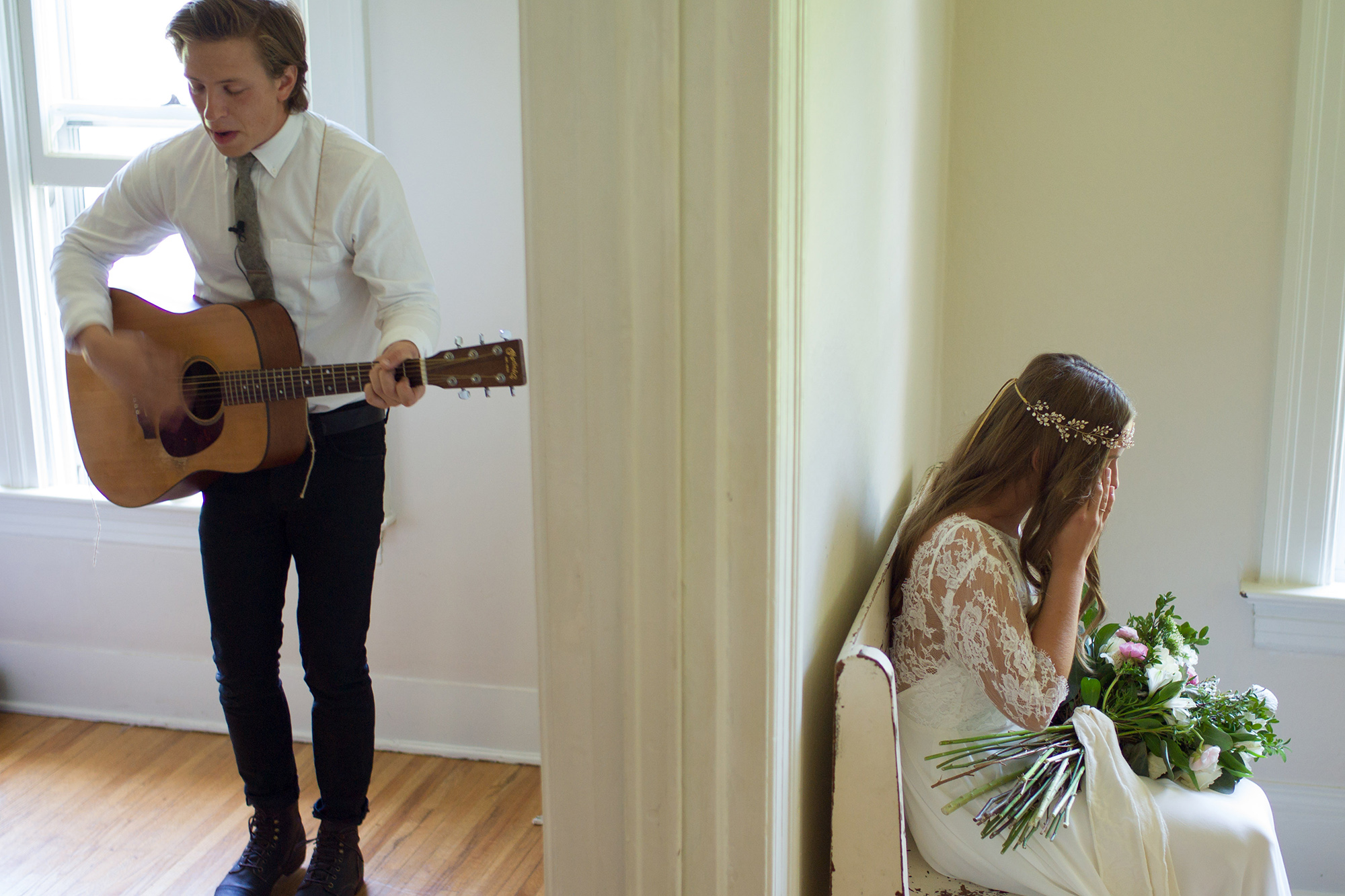 A groom is playing the guitar for his bride, who is sitting on a chair in the next room.