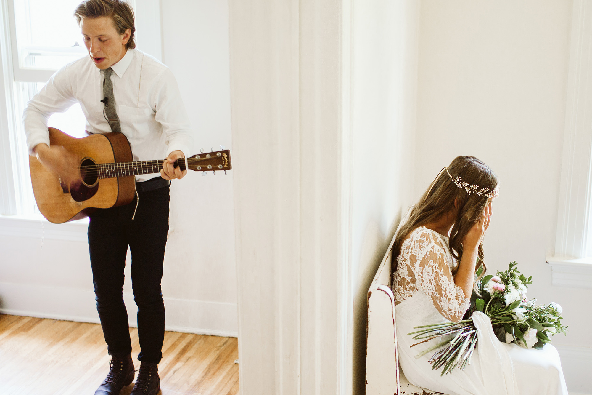 The groom is playing guitar for his bride who is sitting in the next room.