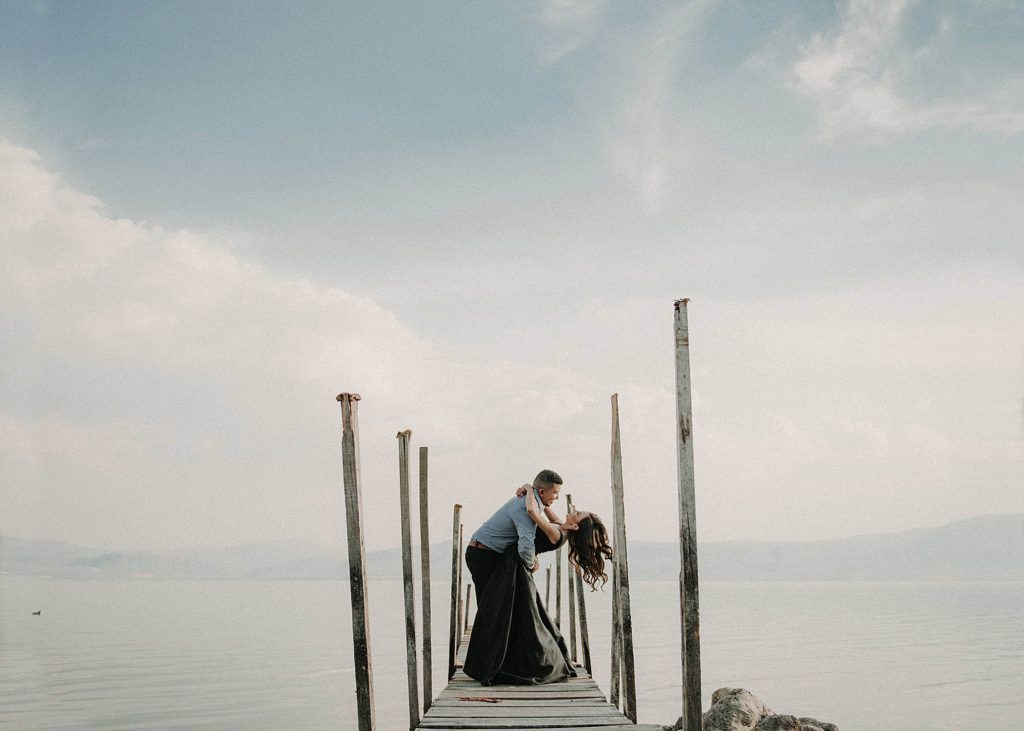 A couple is holding each other and standing on a little pier next to a lake and the mountains.