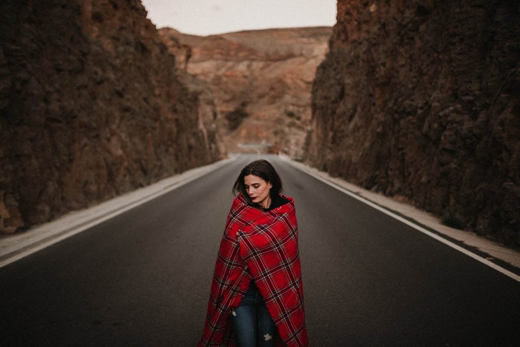 A woman is holding a red blanket and standing in the middle of the street.