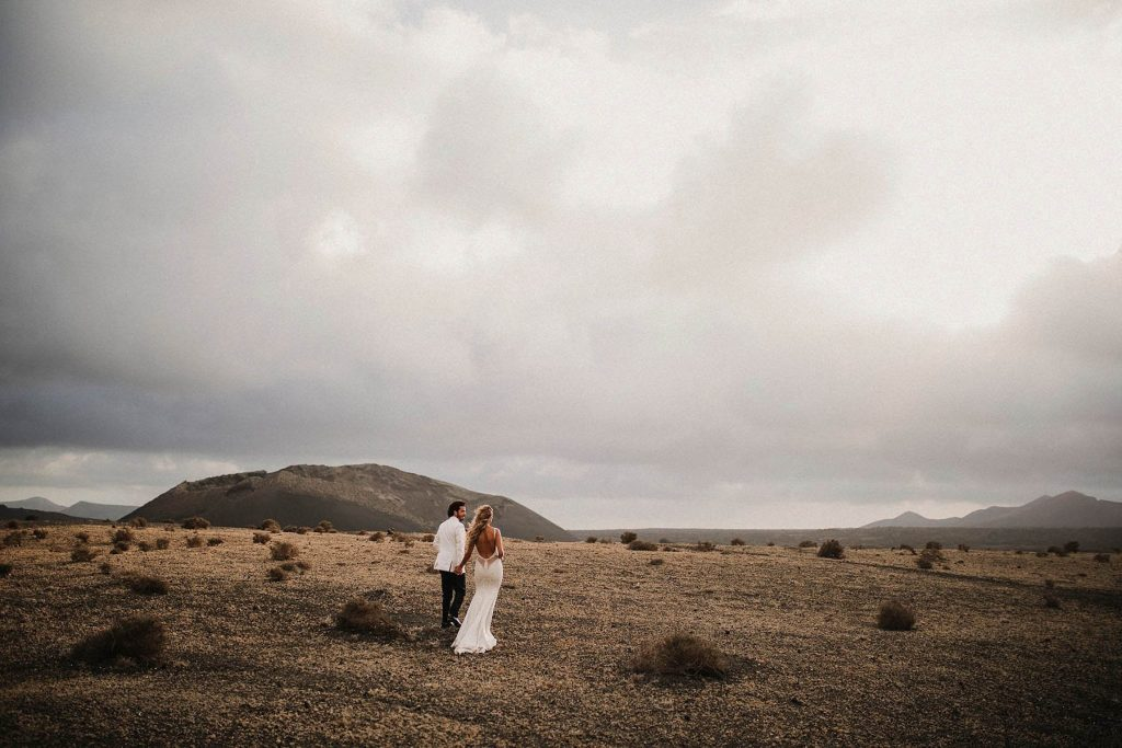 A wedding couple is holding hands and standing in a dry patch of land.