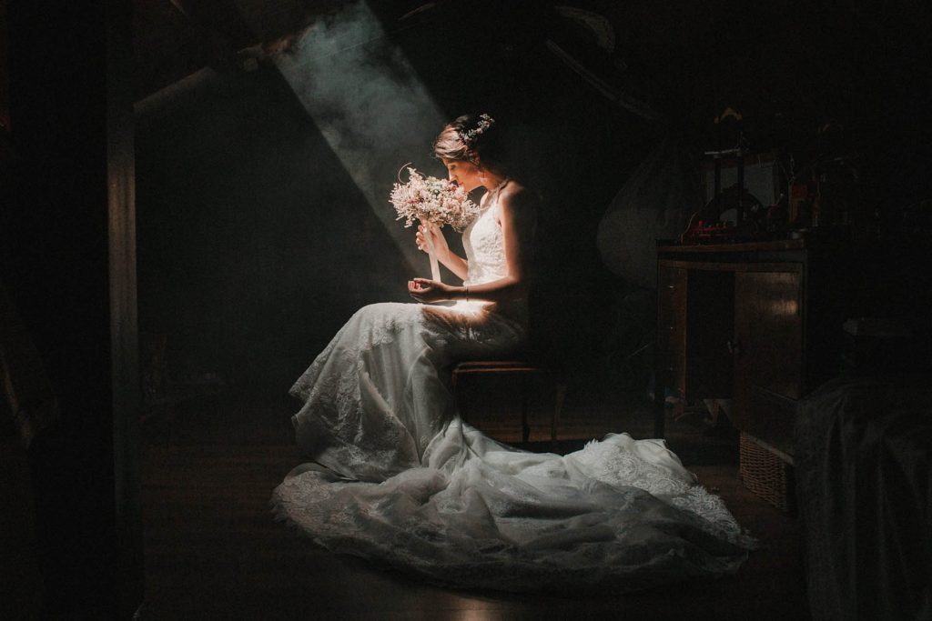 A bride is sitting on a chair in the attic and smelling her flower bouquet.