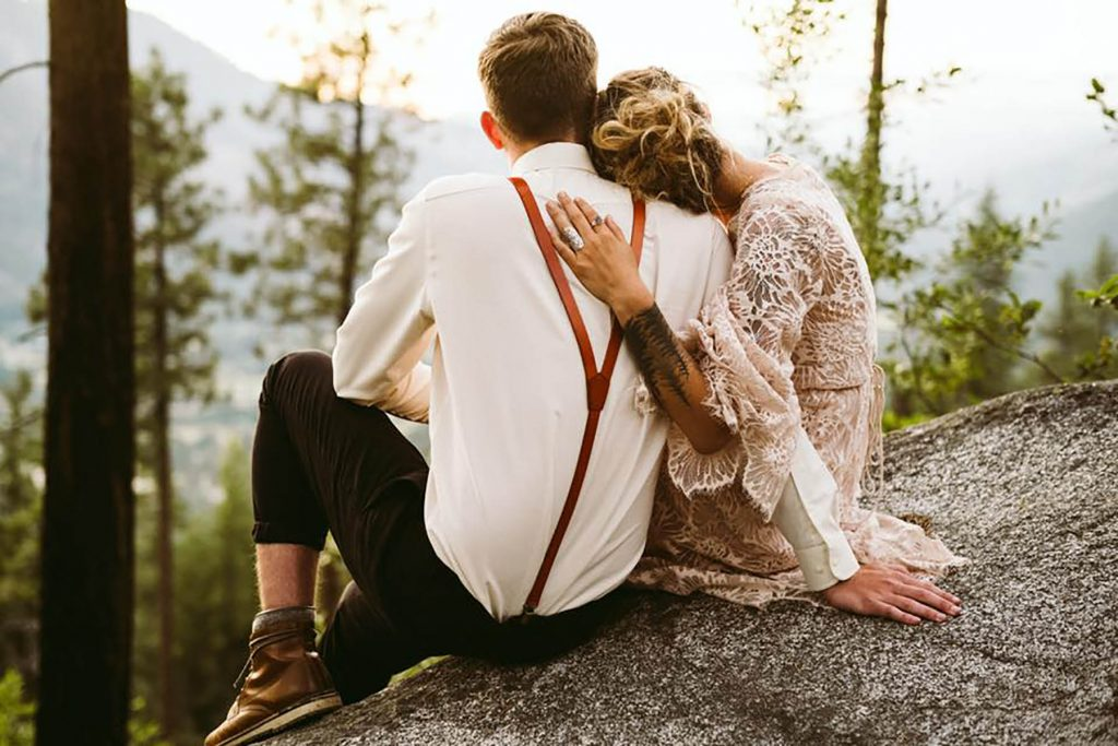 A wedding couple is holding each other and sitting on a rock.