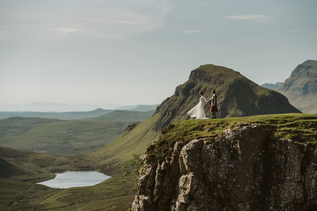 A wedding couple is standing near a cliff and is holding hands.