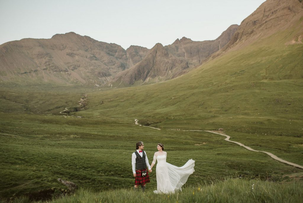A wedding couple is holding hands and standing in a meadow.