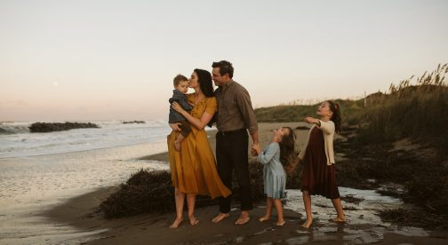 Two parents and their three children are standing at the beach.