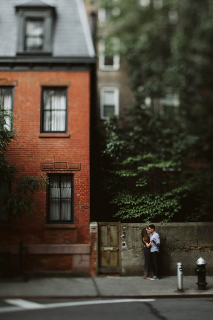A couple is kissing each other and standing in front of a wall, next to a house.