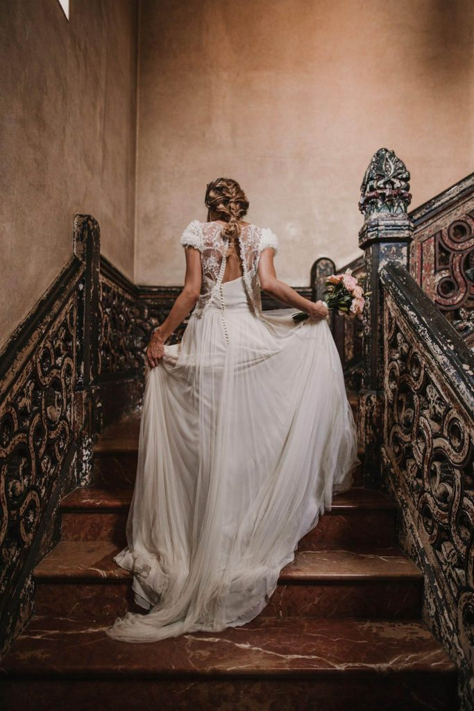 A bride is walking up a staircase.