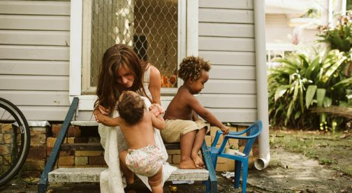 A woman and her two children are sitting on chairs outside the house.