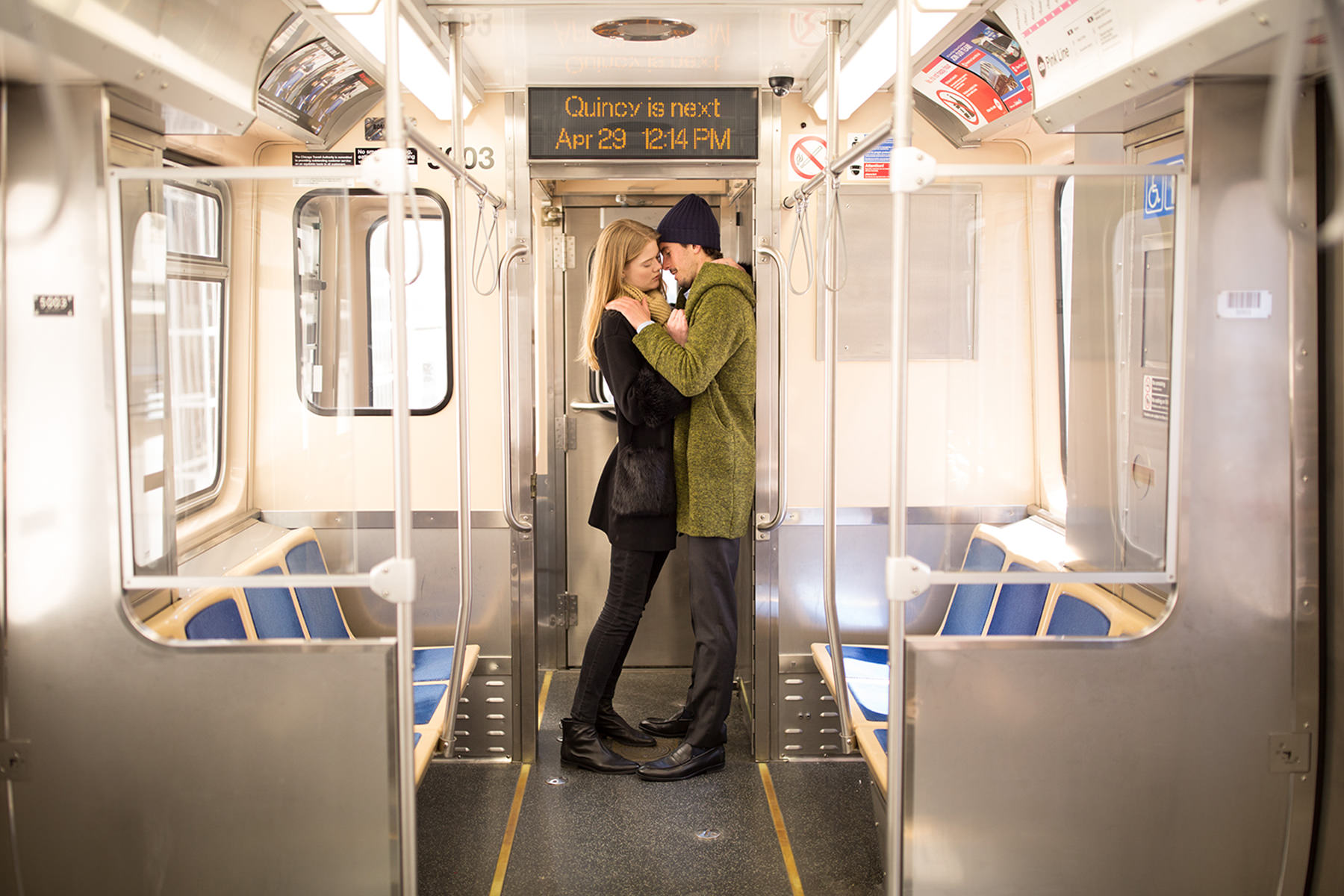 A couple is standing in a train cabin and is about to kiss each other.