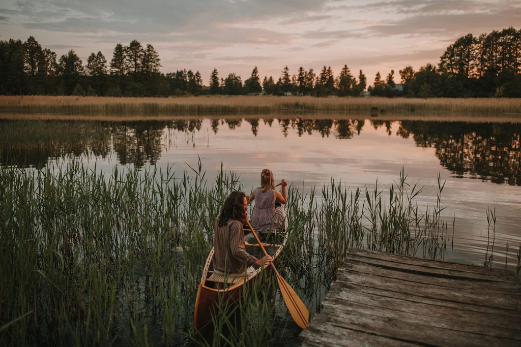 A couple is sitting in a boat on a lake.