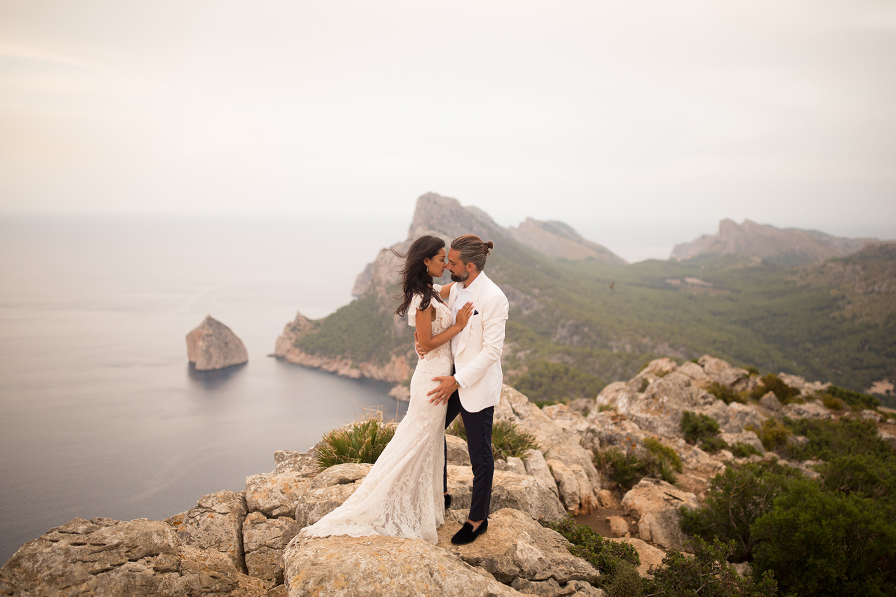 A wedding couple is holding each other and standing on top of a cliff next to the ocean.