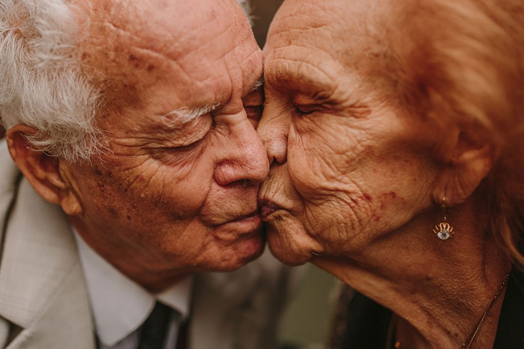 An elderly couple is kissing each other.