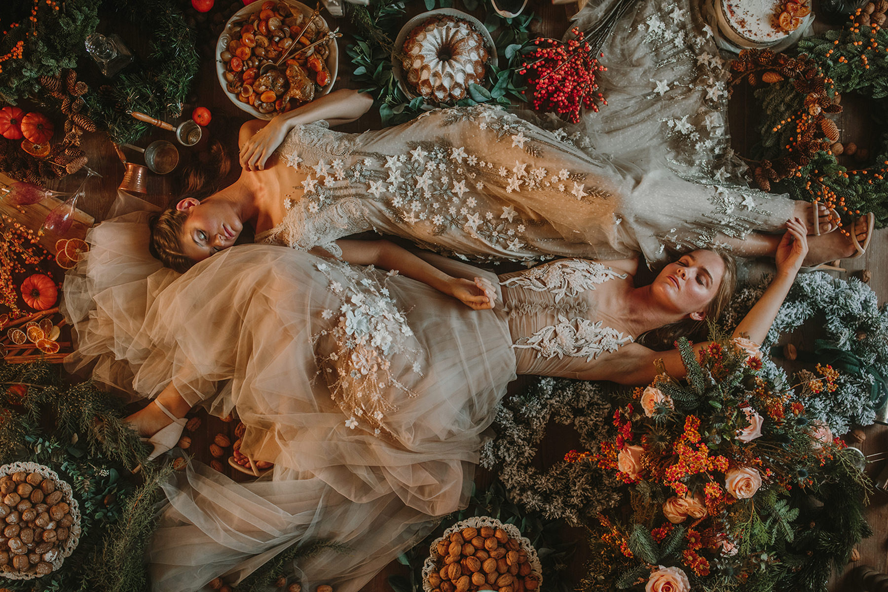 Two brides are lying on the ground next to flower decor and festive food.