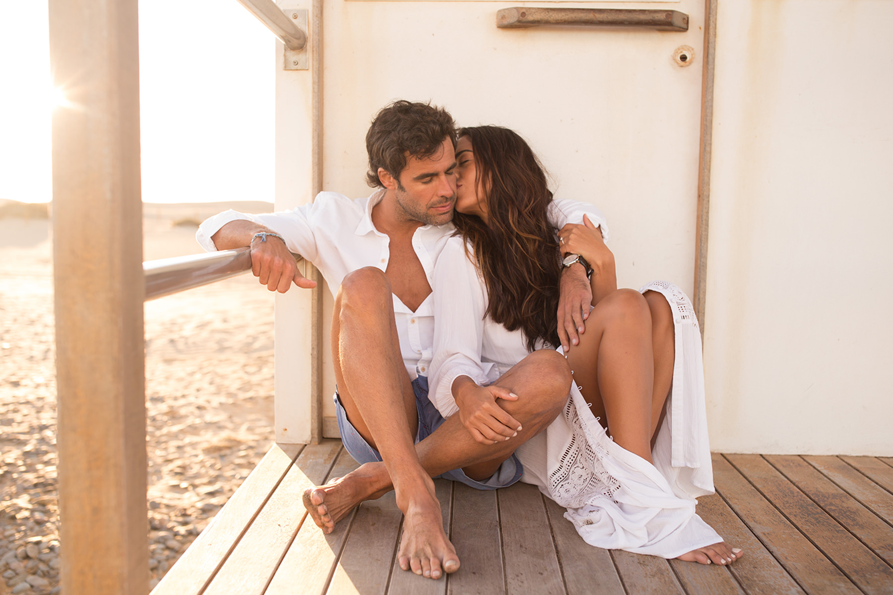 A couple is sitting on a porch at the beach and the woman is kissing the man.