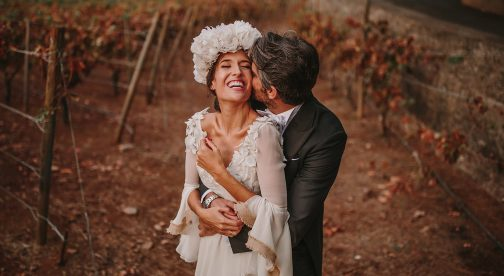 A groom is kissing his bride and they are standing in a vineyard.