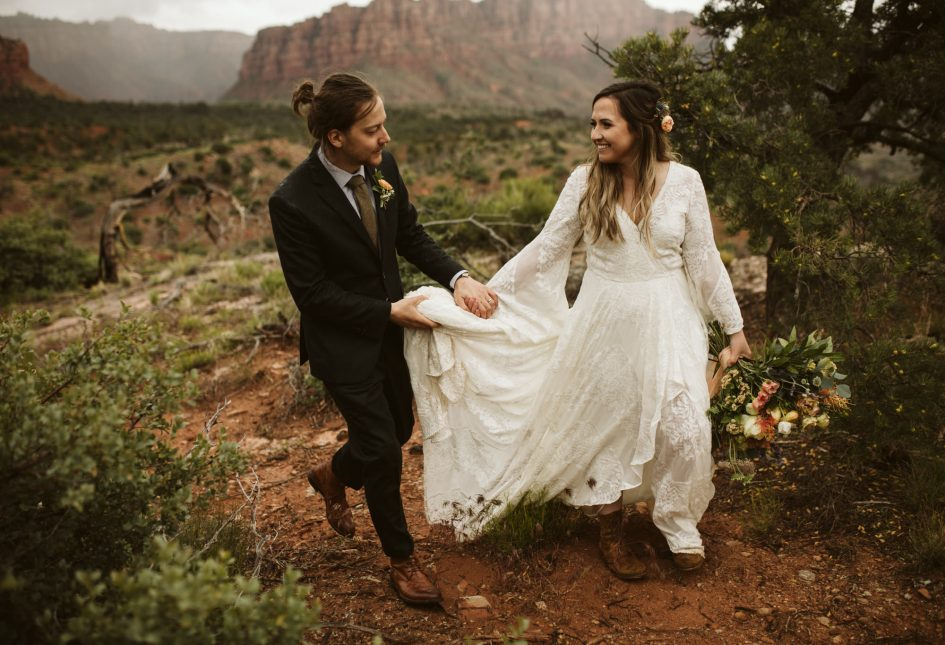 A wedding couple is holding hands and walking along a path in the mountains.