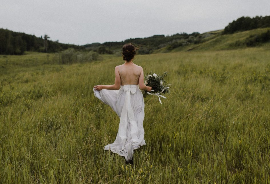 A bride walks over a field of grass with her bridal bouquet.