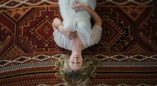 A portrait of a woman that lays on a carpet photographed from above.