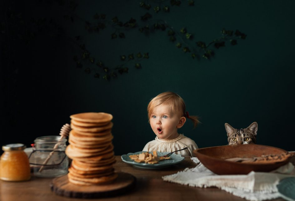 A small child is looking at a pile of pancakes with sparkling eyes.