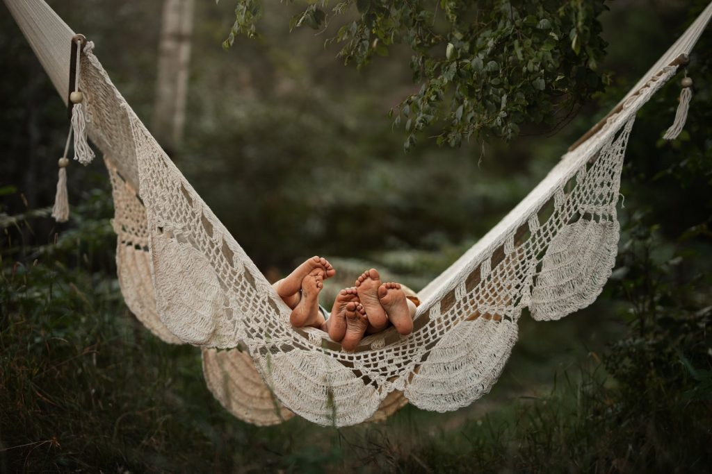 Three children are lying on a hammock with their feet facing the camera.