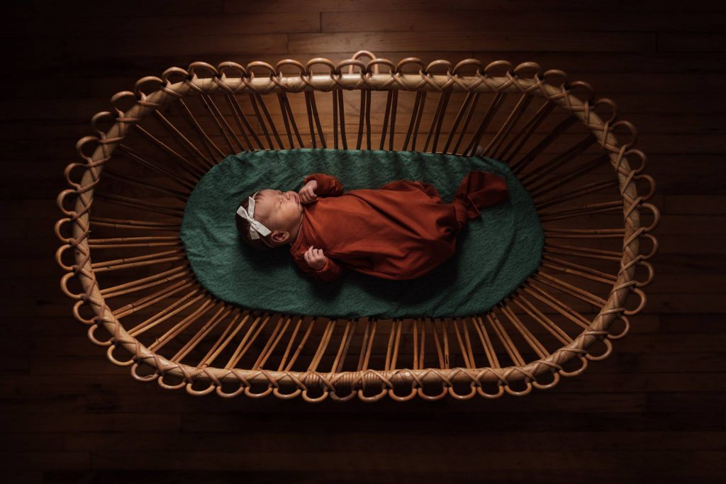 A baby is lying in a bassinet.