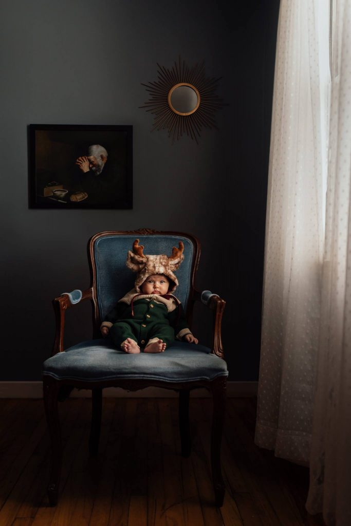 A toddler is sitting on an armchair next to a window.