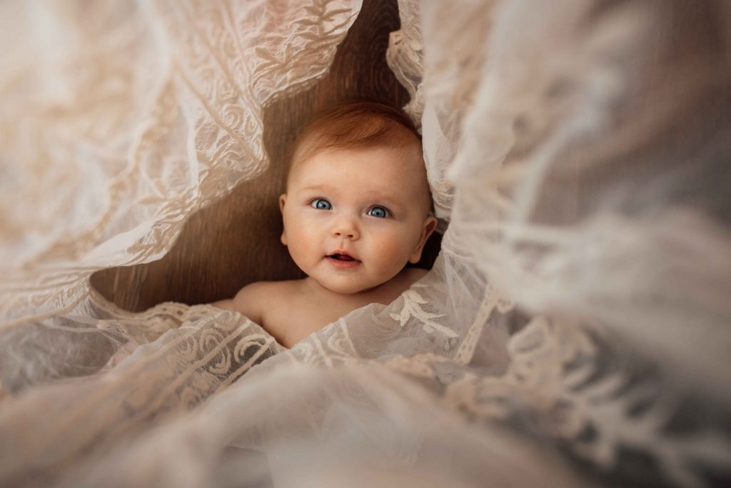 A baby is looking at the camera and lying in between white curtains.