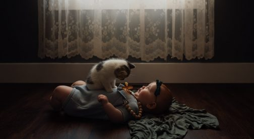 A baby is lying on the floor with a kitten sitting on top.