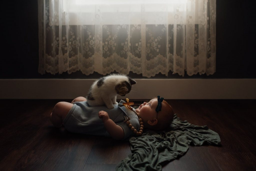 A baby is lying on the floor and a kitten is sitting on the baby.