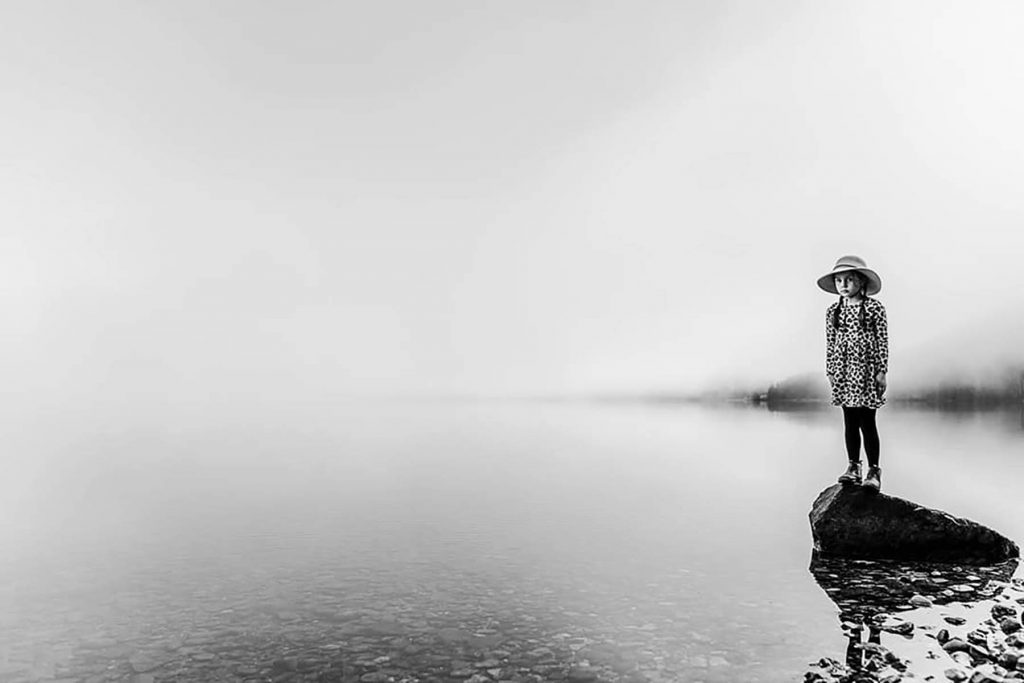 A black and white photo of a kid that stands on a rock in the lake.