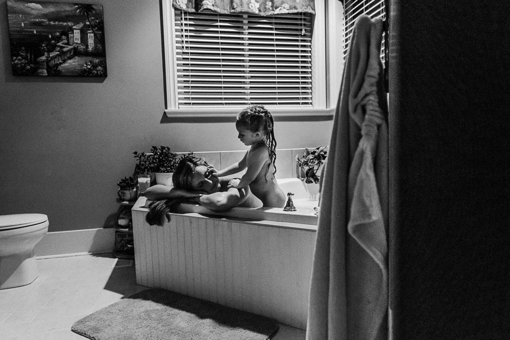 A black and white photo of a mom and her daughter taking a bath.