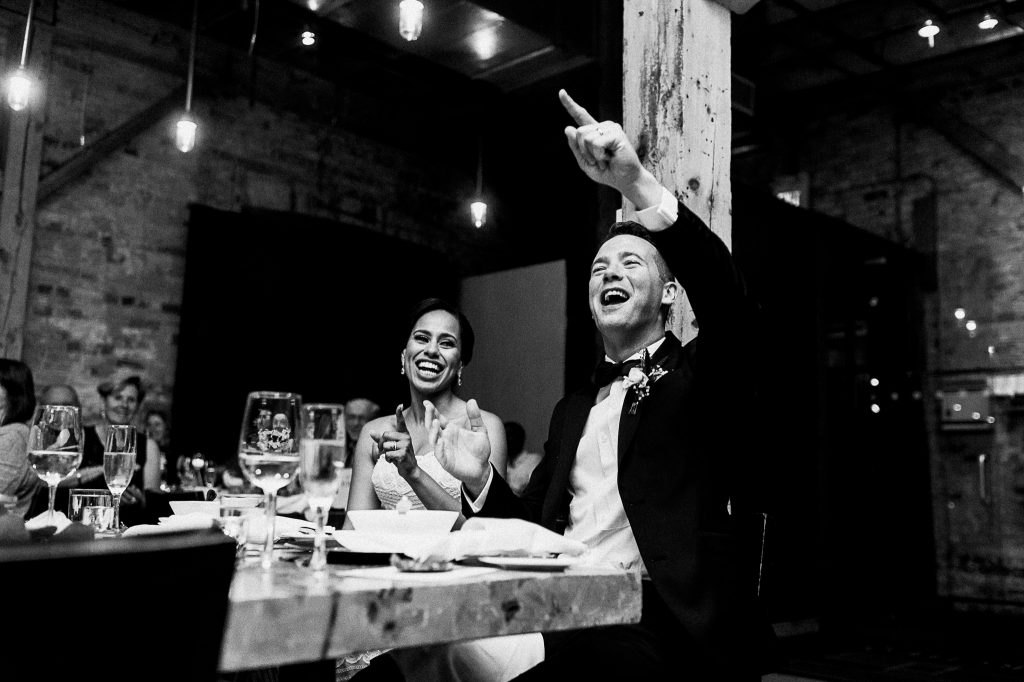 A black and white photo of a bride and a groom that sit at the wedding table.
