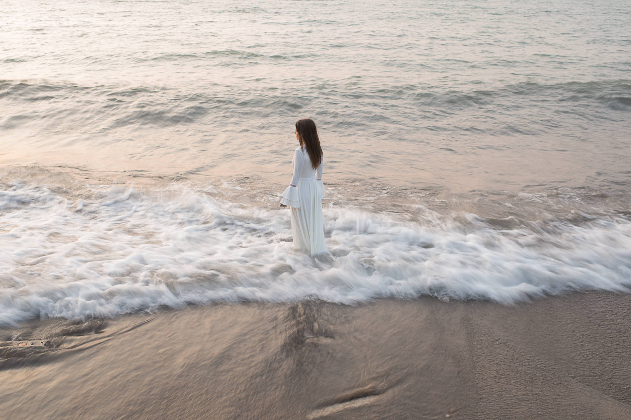 An unedited photo of a woman who stands in the waves of the sea.