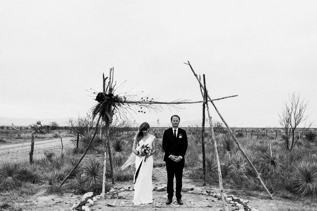 A black and white portrait photo of a wedding couple who poses underneath a wooden arc in the desert.