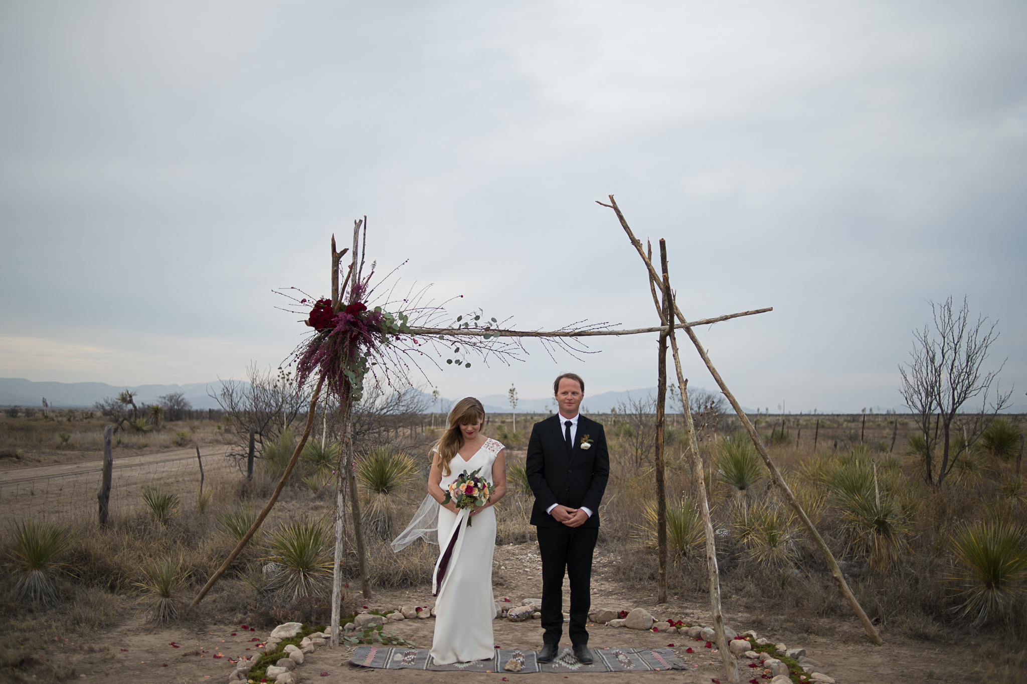 An unedited photo of a wedding couple who poses underneath a wooden arc in the desert.