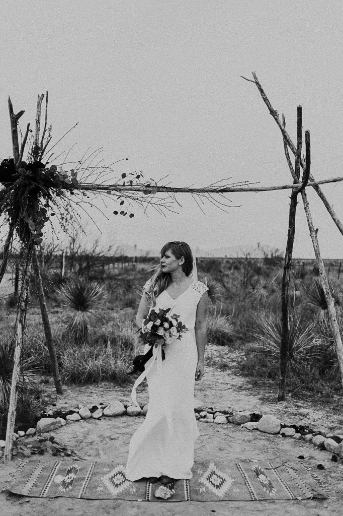 A black and white portrait photo of a bride who stands underneath a wooden arc in the desert.