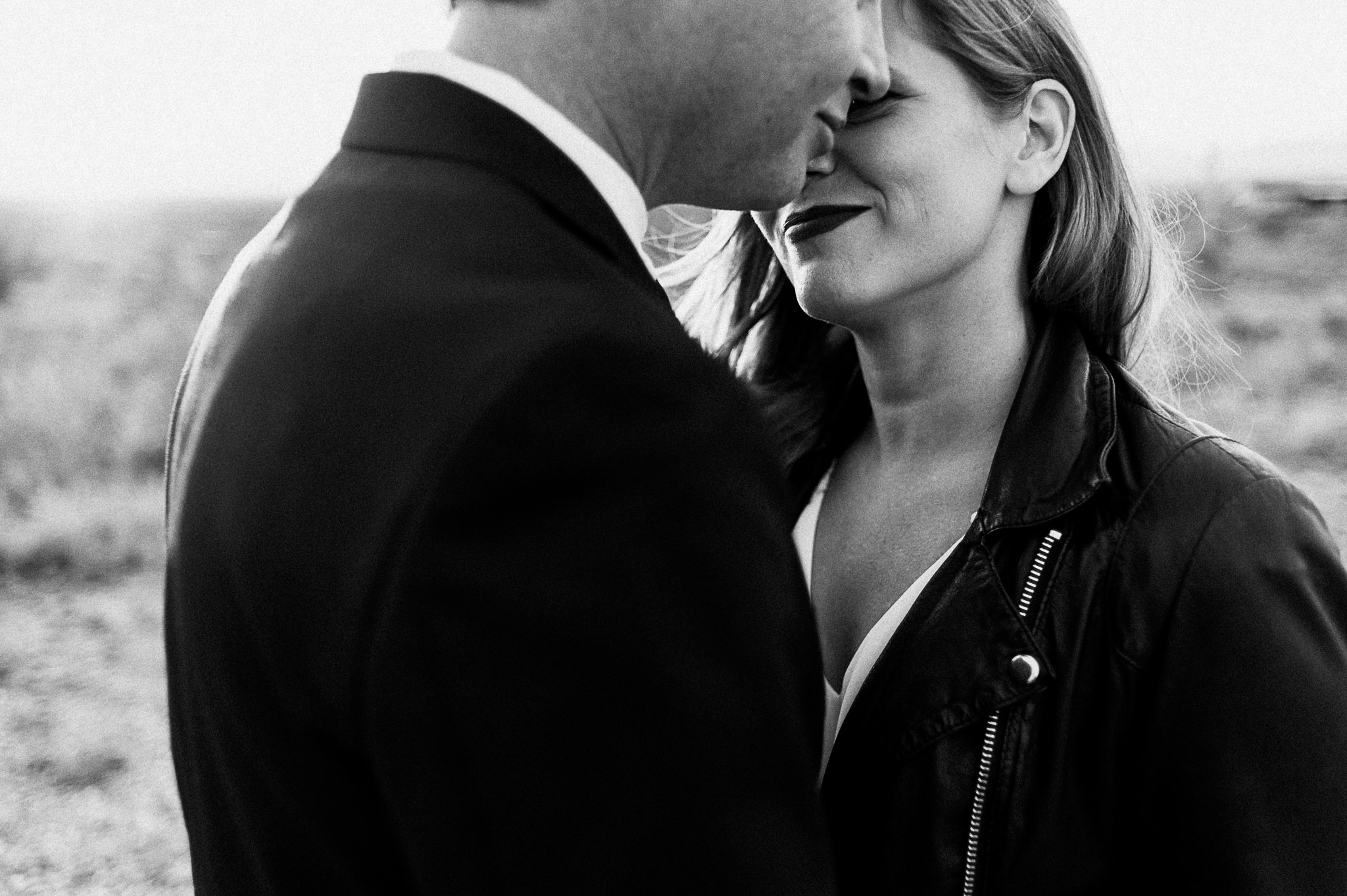 A black and white photo of a couple who puts their heads close together.